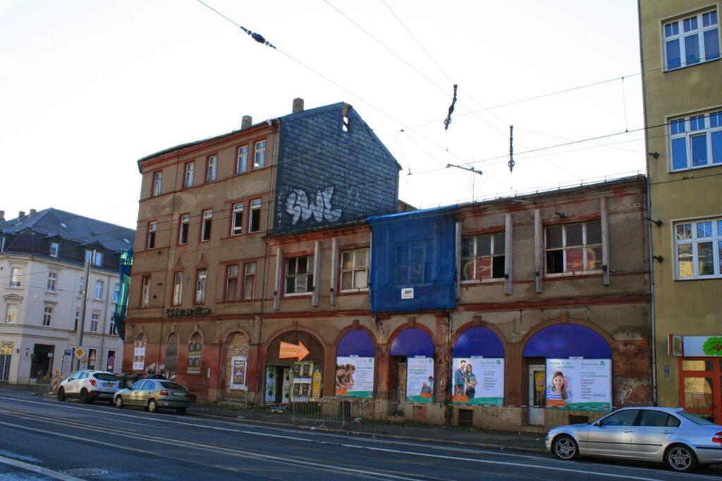 """Blick von der Georg-Schumann-Straße (Huygensplatz) auf das verfallende Gebäude vom """"Goldenen Löwen"""" - Anfang der 50ger Jahre wurde das Hotel bzw. Ballhaus zur Vertragsgaststätte der HO bis das Haus gegen 1985 geschlossen wird und seitdem ungenutzt verfällt"""