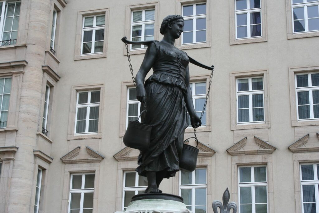 lebensgroße Bronzefigur des Mädchens auf dem Brunnen