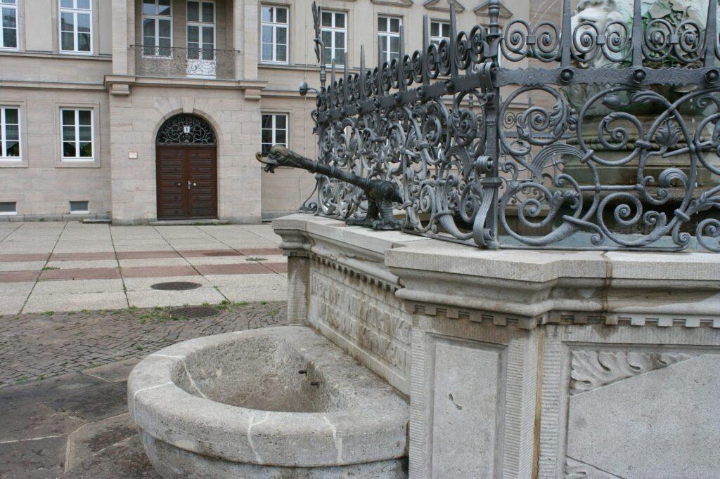 vorgelagertes Becken mit Hebelarm am schmiedeeisernen Gitter