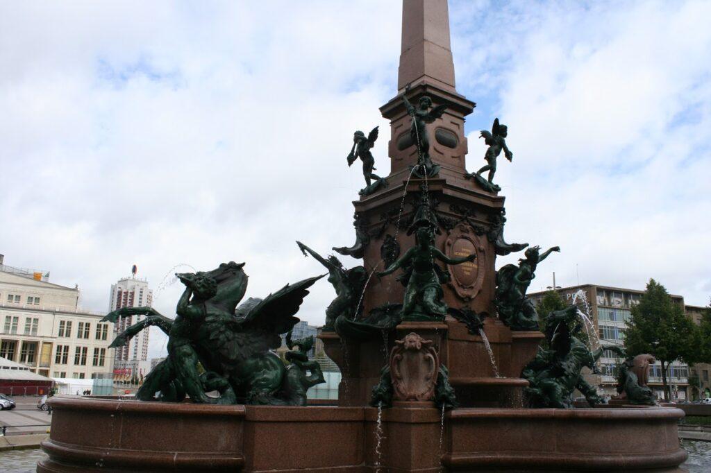 Mendebrunnen mit Figuren - dahinter links das Gewandhaus im Bild