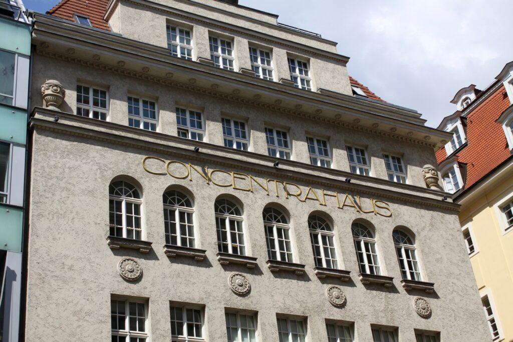 """goldene Aufschrift """"CONCENTRAHAUS"""" am Gebäude in der Innenstadt - gut zu erkennen die zwei klassizistische Vasen im vierten Obergeschoss"""